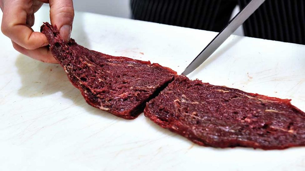 A fillet of raw horse meat being cut