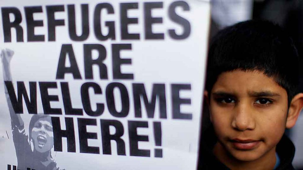 Boy holds a placard in a march by Glasgow residents in support of asylum seekers in 2010