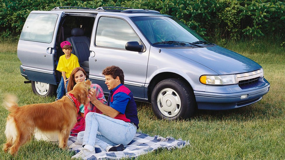 A 1980s family relaxing next to their car. Getty Images