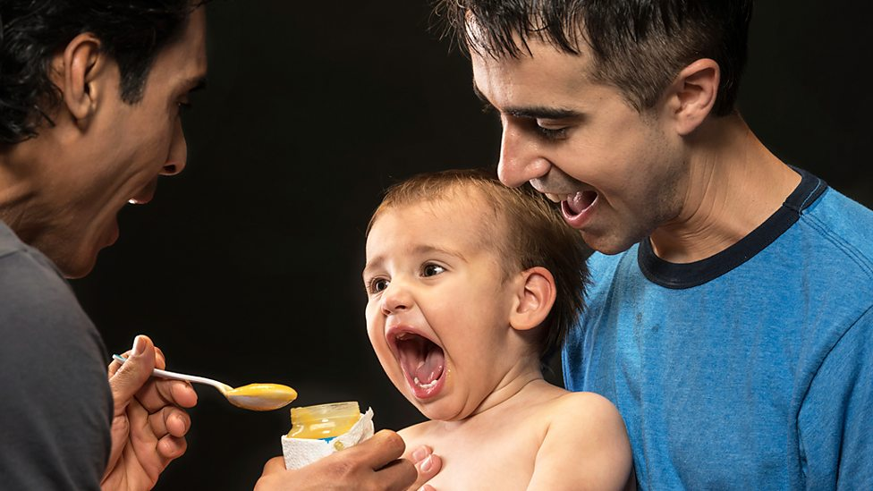 Two dads in a same-sex relationship feeding their son. Getty Images.