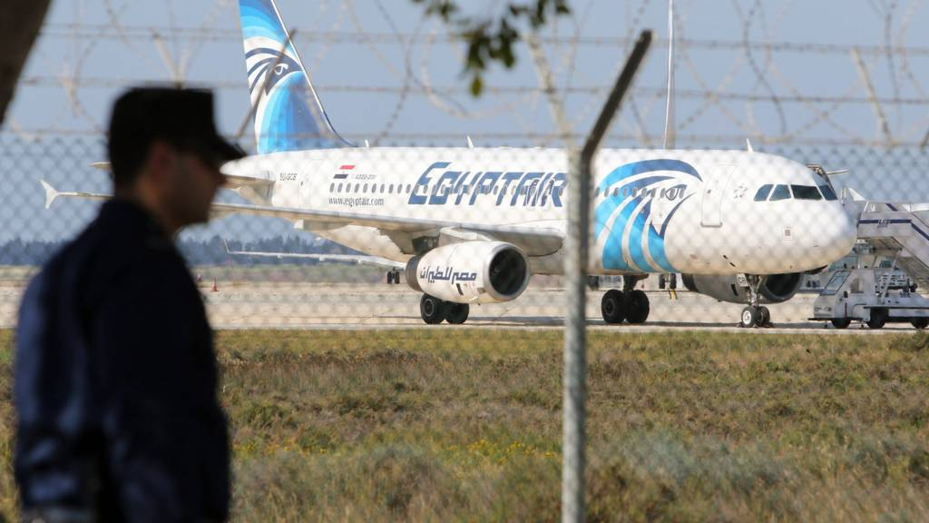 A Cypriot policeman stands guard near a hijacked EgyptAir A320 plane at Larnaca Airport, in Larnaca, Cyprus, 29 March 2016