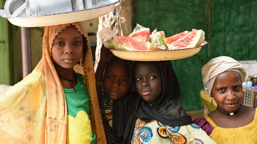Women at a market in Chad - one with a platter of watermelon pieces on her head