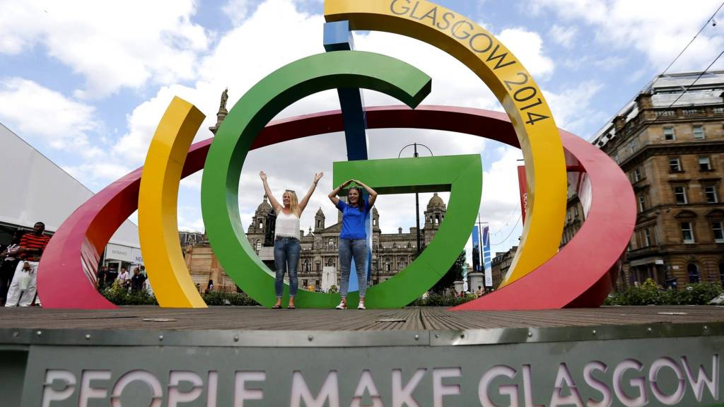 """Alicia Steerand Gemma MacLean pose on """"The Big G"""" 3-D structure at George Square in Glasgow, Scotland"""
