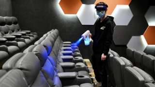 An employee sprays disinfectant to seats at a cinema during its reopening on February 18, 2021 in Hong Kong, China.