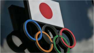 Olympic Rings and the Japanese flag are seen outside the Olympic Museum in Tokyo on August 24, 2020.