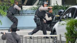 Indonesian police take position and aim their weapons as they pursue suspects in Jakarta