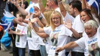Supporters of Batonbearer 056 Edward Fitzpatrick wave as he carries the Glasgow 2014 Queen's Baton through Dennistoun in Glasgow.