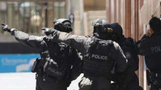 Armed police officers close to the site of a hostage situation in Sydney