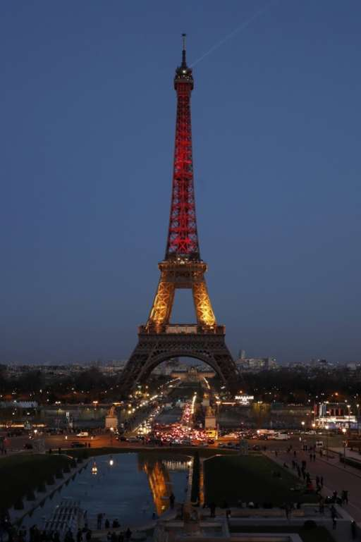 The Eiffel Tower is lit in black, yellow and red - the colours of the Belgian national flag