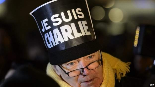 "A man adorns his hat with a placard with ""Je suis Charlie"" (I""am Charlie), written on it, during a rally in solidarity with the killed Charlie Hebdo employees, in Lausanne, Switzerland, 07 January 2015"