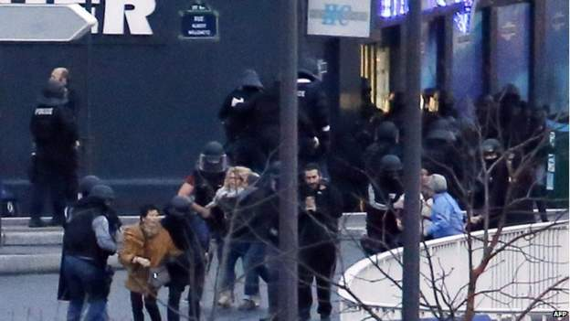 Members of the French police special forces evacuate the hostages after launching the assault at a kosher grocery store in Porte de Vincennes, eastern Paris, on 9 January 2015