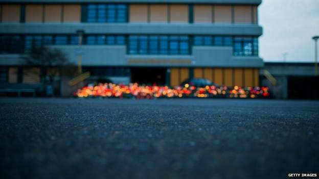 A memorial of flowers and candles in front of the Joseph Koenig secondary school