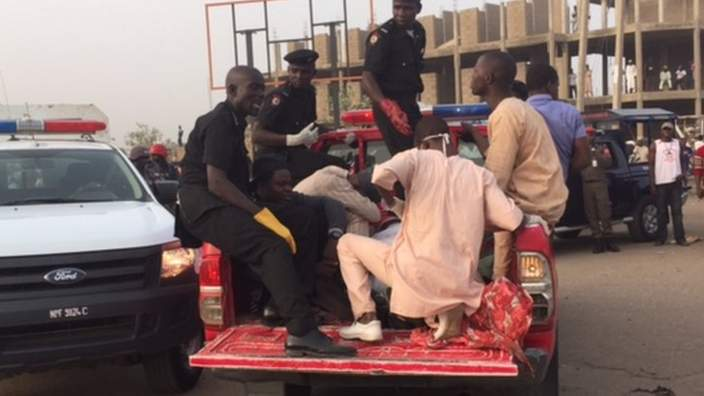 People helping someone injured in the mobile phone market in Kano, Nigeria