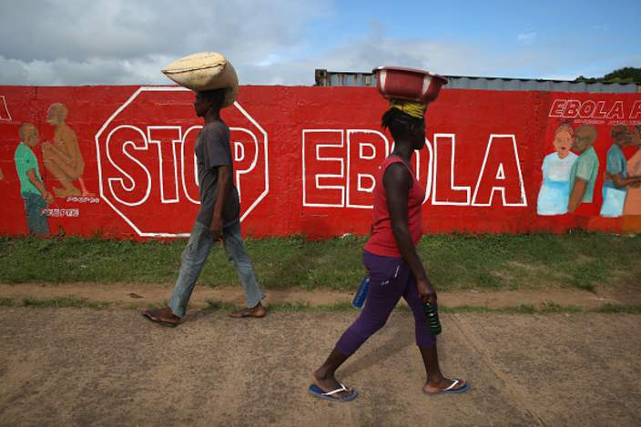 People walk past a wall with a sign about Ebola