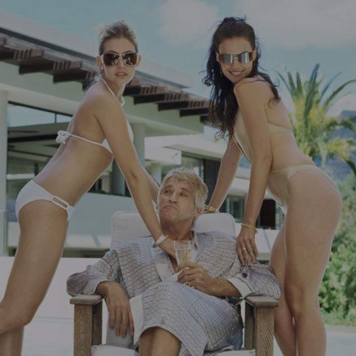 Photo of an actor posing as a 'sugar daddy' with two girls in bikinis
