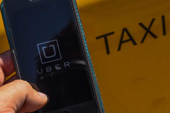 In this photo illustration, the new smart phone app 'Uber' logo is displayed on a mobile phone next to a taxi on July 1, 2014 in Barcelona, Spain
