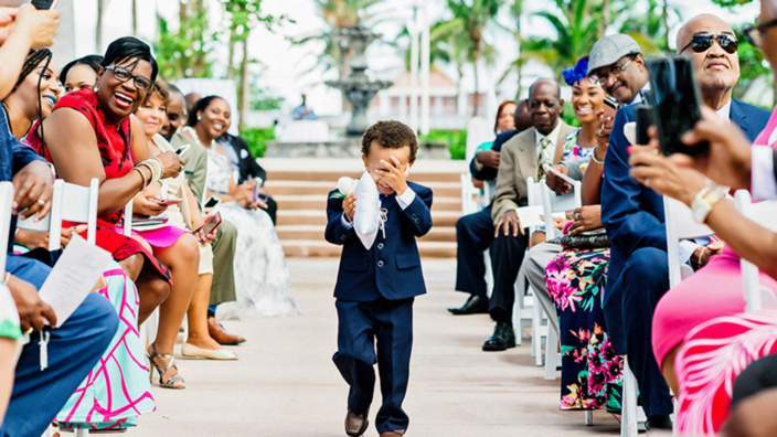 Page boy covers his face while carrying the ring cushion down the aisle at wedding
