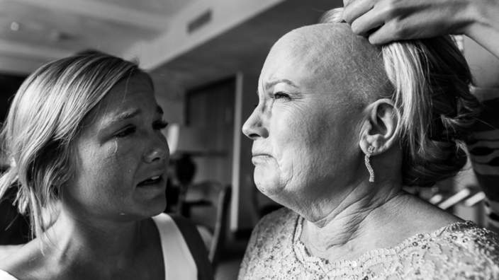 A woman who has lost her hair following chemotherapy has a wig fitted on her daughter's wedding day, while her daughter watches tearfully