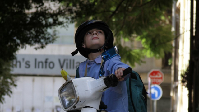 Boy on scooter looking up