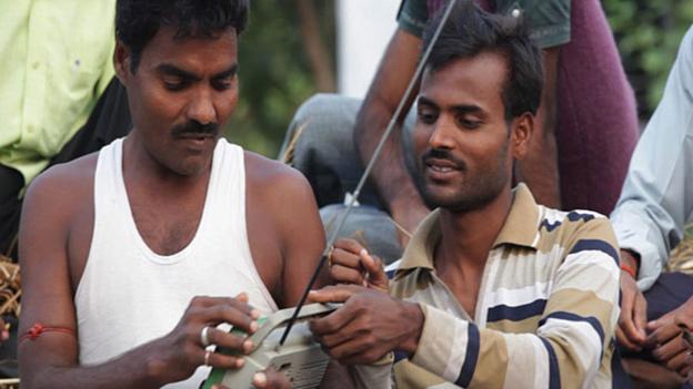 Two men tune a radio