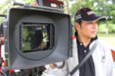 A Cambodian man stands behind a camera.