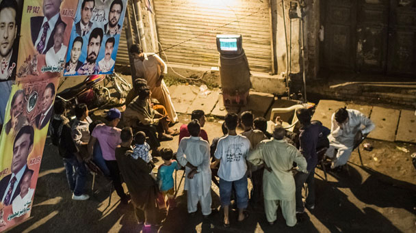People watching a TV on a street in Pakistan