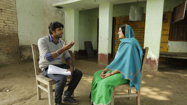 A man interviews a woman in India.