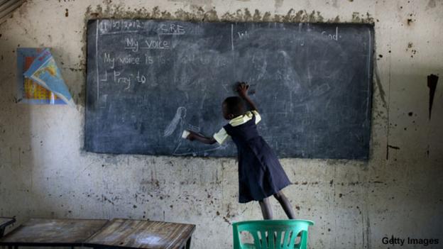A girl wipes a blackboard in a school in South Sudan.