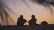 Silhouette of two nomadic people sitting around a camp fire at sunrise