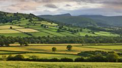 Farmland in the Usk Valley backed by Pen y Fan and Cribyn mountains, Brecon Beacons National Park, Powys, Wales