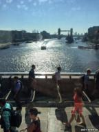 London commuters walk across London Bridge during a sunny day. Tower Bridge can be seen in the background