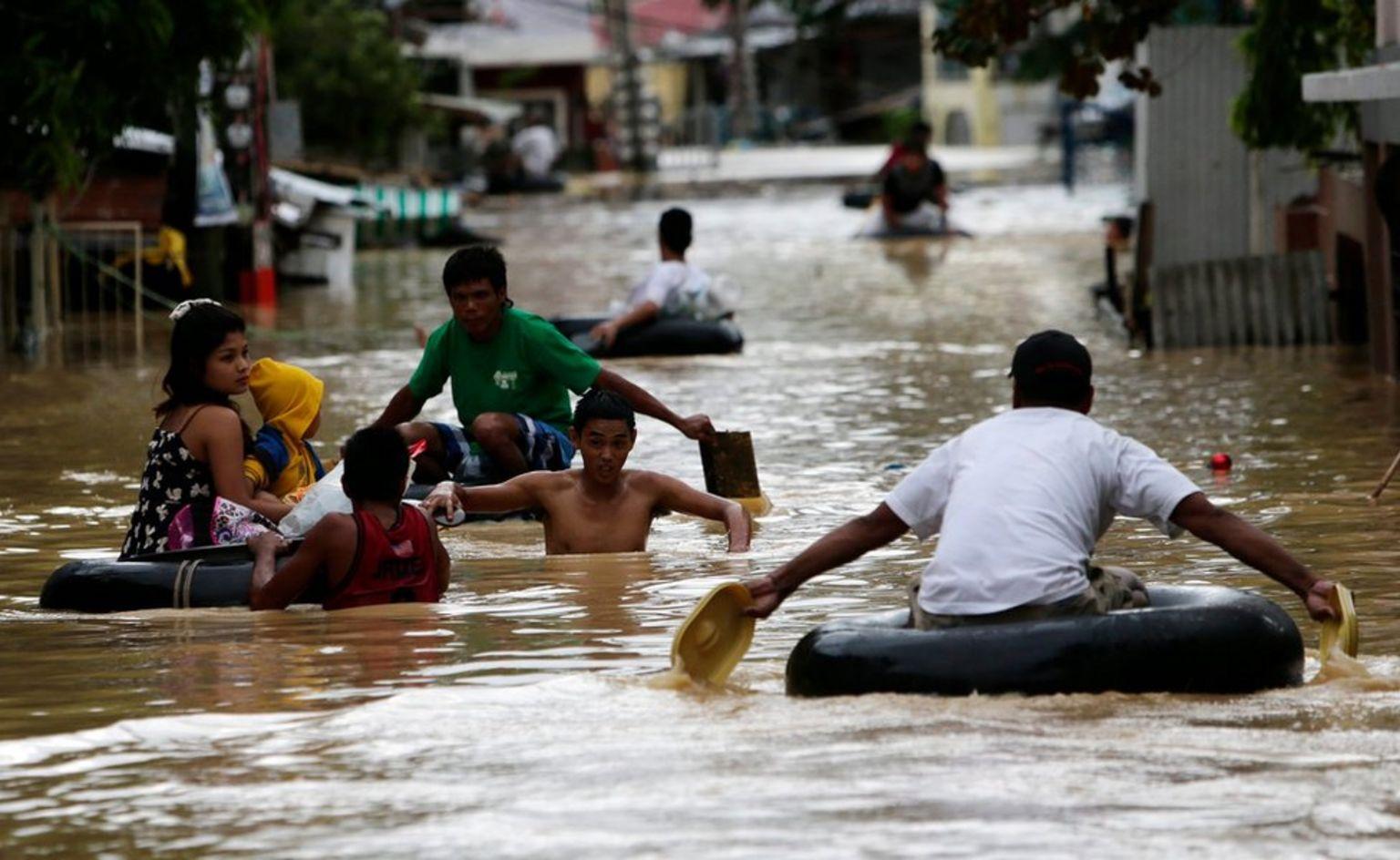 Filipino typhoon victims wade on flood water in Cabanatuan city, northern Manila