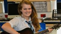 Daisy Clerk with her guitar at school