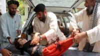A wounded Afghan child being brought to a hospital after being injured in a mortar explosion in Kandahar on 1 July 2015
