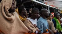 Refugees and migrants wait on deck of the Spanish NGO Proactiva Open Arms rescue vessel Golfo Azzurro to disembark after being rescued off Libyan coast north of Sabratha, Libya on February 19, 2017