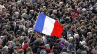 A man holds a French national flag in the middle of a large crowd