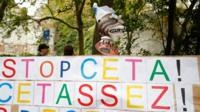 """A placard reading """"Stop CETA - it""""s enough"""" during an anti-CETA protest in front the Walloon parliament in Namur, Belgium"""