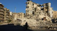 Man cycles past war-damaged buildings in rebel-held Tariq al-Bab district of Aleppo (26 September 2016)