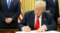 President Donald Trump signs first executive orders in Oval Office in Washington, January 20, 2017