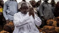 Adama Barrow, hands clasped and surrounded by supporters at a rally in Talinding on 29 November