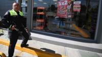 A policeman checks on a store that was looted during a protest over the 20 percent gasoline price hike in Ecatepec, state of Mexico, on January 5, 2017.