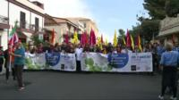 Wide shot of the protest marchers, carrying flags and photographs