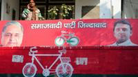 In this photograph taken on 12 January 2017, a party worker of India's Samajwadi Party stands on the balcony of a Samajwadi Party office adorned by the present party symbol, a bicycle in Allahabad