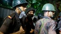 Bangladeshi security personnel stand guard near a restaurant that has reportedly been attacked by unidentified gunmen in Dhaka, Bangladesh, on 1 July