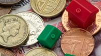 Monopoly houses and hotels on top of UK coins and banknotes