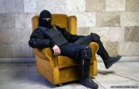 A masked pro-Russian protester sits on a chair as he poses for a picture inside a regional government building in Donetsk, eastern Ukraine