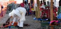 A nurse wearing personal protective equipment (PPE) checks on a patient at the Kenema Ebola treatment centre run by the Red Cross on November 15, 2014
