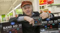 Bob Geldof holds a Band Aid CD single and gives a thumbs up to the camera