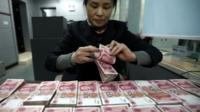 A clerk counts Chinese currency