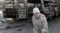 An elderly woman walks past vehicles destroyed in shelling between Russian-backed separatists and the Ukrainian government forces in Donetsk on 11 February 2015